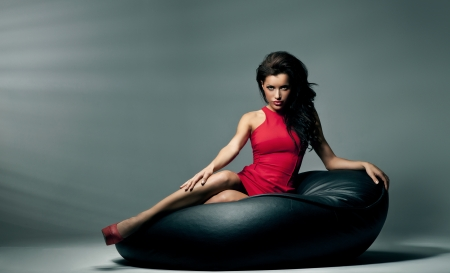 girl lying: Sexy brunette woman lies on the black pillow Stock Photo