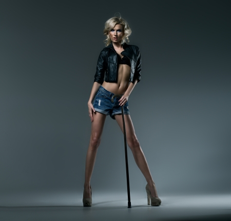 Sexy blond woman with the stick in studio photo