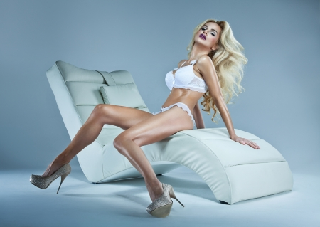 Sexy blonde woman with winter makeup sitting on a stylish chair
