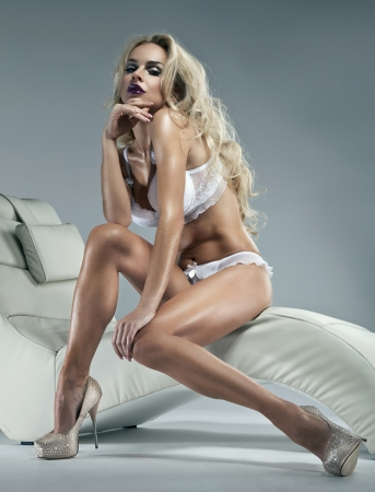 Sexy blonde woman with winter makeup sitting on a stylish chair  photo