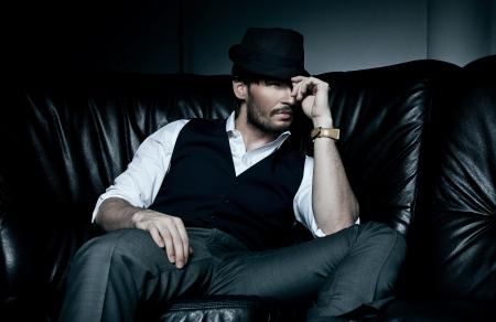 viso uomo: Sexy bruna uomo giace sul divano nero
