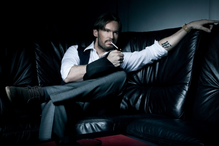 gangster background: Sexy brunette man on the black couch smoking a cigarette  Stock Photo