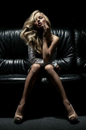 sexy breasts: Beautiful blonde woman on black couch  Stock Photo