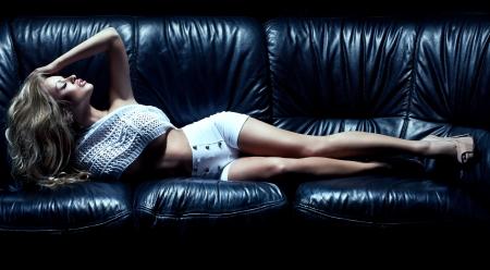 salud sexual: Hermosa mujer rubia en el sof? negro Foto de archivo