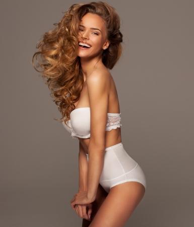 piernas sexys: Mujer atractiva en ropa interior blanca con maquillaje natural Foto de archivo