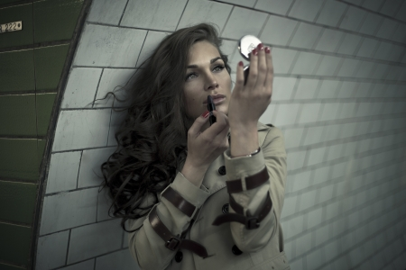 Woman looking in mirror and putting lipstick in underground photo