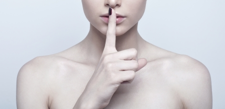 quiet adult: Woman with finger on lips Stock Photo