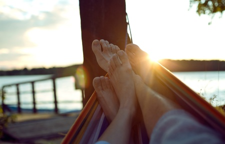 sands: Vacation photo of couple feet relaxing on beach on hammock