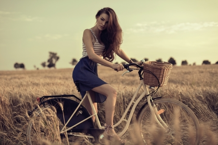 Attractive woman with bike in wheat field Stock Photo