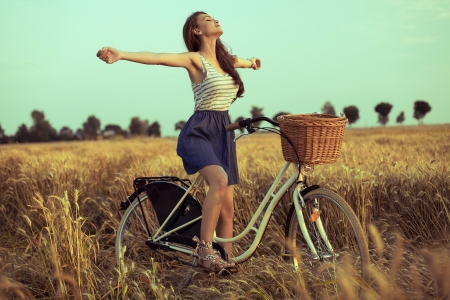 日没で麦畑の上に自転車に自由を楽しんでいる自由な女