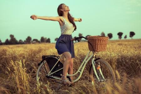 libertad: Mujer libre disfrutando de la libertad en la bici en campo de trigo al atardecer Foto de archivo