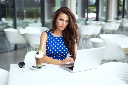 Beautiful woman working on laptop and drinking cafe photo