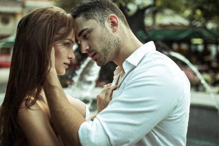 adult dating: Young couple kissing each other on the street Stock Photo