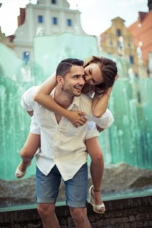 Happy boyfriend piggybacking his girlfriend photo