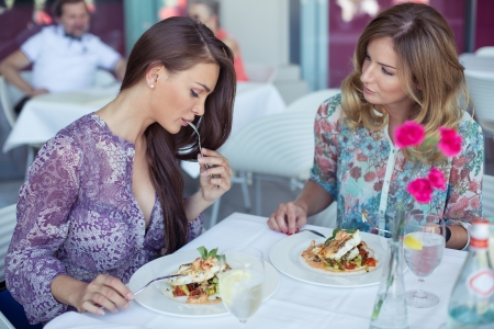 Two beautiful young women eating a dinner photo