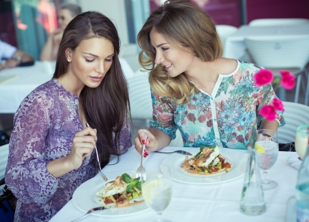 Young cheerful womeno on lunch at restaurant