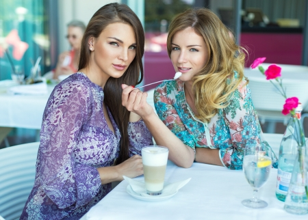 Two beautiful women in restaurant drinking coffee and water photo