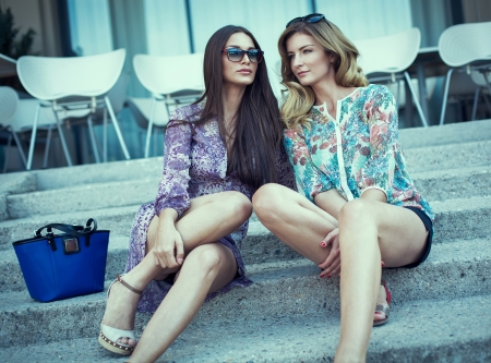 sidewalk talk: Two sexy woman sitting on the stairs Stock Photo