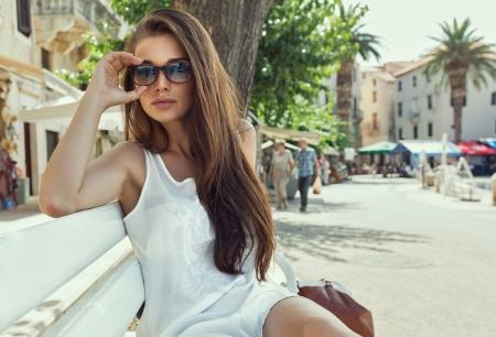 poses de modelos: Mujer joven con gafas de sol y descansando en el banco
