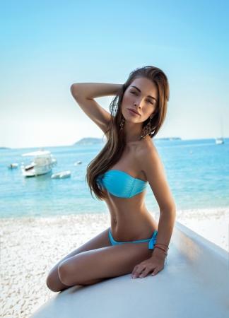 해변에 파란색 수영복을 입고 섹시 한 여자 스톡 콘텐츠