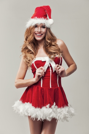Happy woman in santa clause costume holding ribbon photo