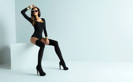glamour model: Sexy woman wearing sunglasses and black stockings