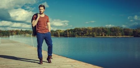 beau jeune homme: Photo panoramique d'un homme beau sur le lac