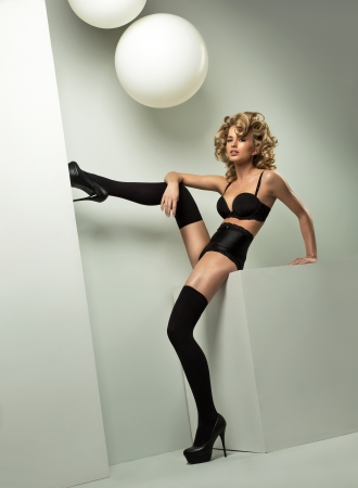 Blond woman in black lingerie basing leg on wall photo