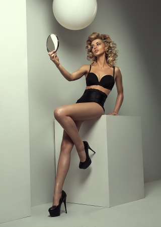 Blond woman looking in the mirror photo