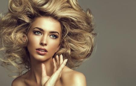 Retrato de uma mulher loura nova com cabelo bonito e olhos verdes