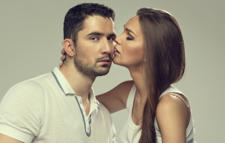 Portrait of kissing couple isolated on grey photo