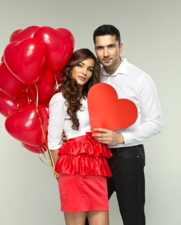 Beautiful couple in love with red balloon heart shape for valentine photo
