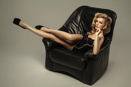Sexy blond woman lying on leather armchair photo