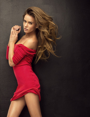 Seductive blond woman in red dress photo