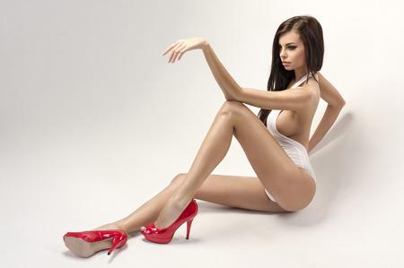 Kırmızı yüksek topuklu giyen seksi kadın