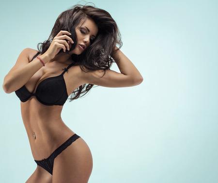 Brunette woman posing in black lingerie Stock Photo