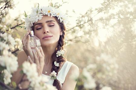 Schöne sinnliche Frau träumt mit Parfüm-Flasche in der Hand