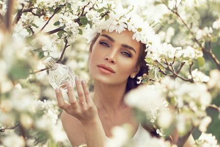 Mujer con la botella de perfume en el jardín Foto de archivo