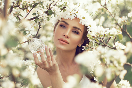Woman with bottle of perfume in the garden photo