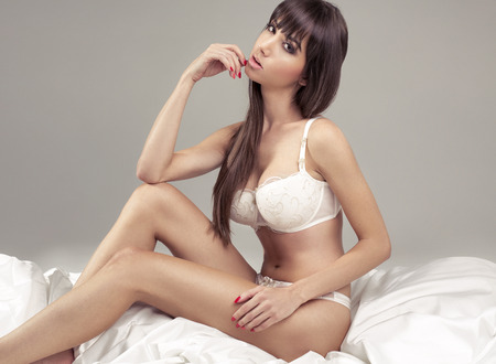 Alluring woman lying in bed photo