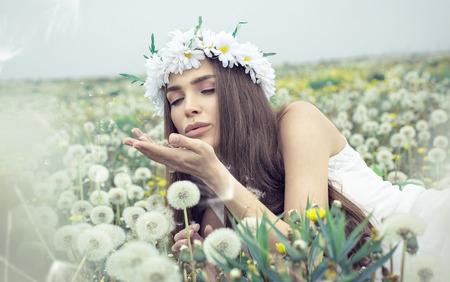 Beautiful woman blowing dandelions photo