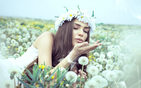 Young woman blowing dandelions Stock Photo - 29379911