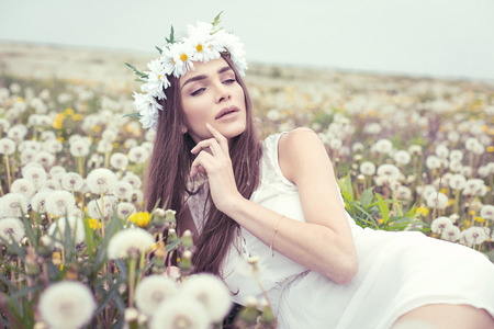 Alluring woman lying on a meadow full of dandelions Stock Photo - 29379912