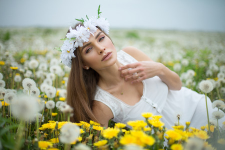 Alluring woman lying on a meadow full of dandelions Stock Photo - 29379913