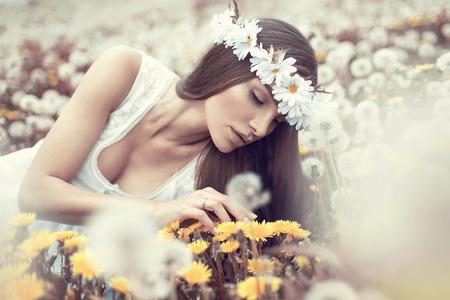 Portrait of beautiful woman on dandelions meadow  photo