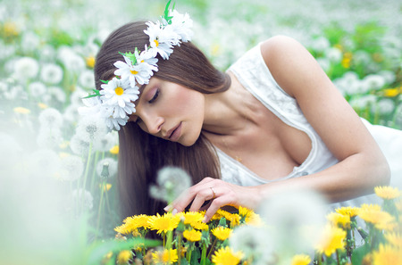 Young beautiful woman lying on a meadow of dandelions Stock Photo - 29379918