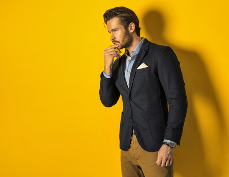 handsome man wearing jacket on yellow background photo