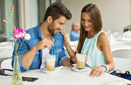 Beautiful couple in cafe enjoying the time spending with each other photo