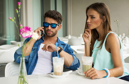 Handsome man with beautiful woman talking on a smart phone  photo