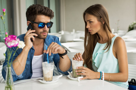 Handsome man with beautiful woman in cafe talking by the smartphone photo